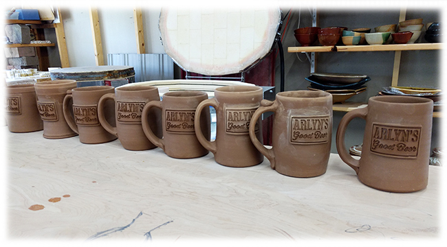 Mugs made with clay stamped logos by John Thies 2019